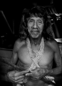 "Davo Enemenga, a Huaorani man whose ancestral land has been contaminated by oil exploration by Chinese government-owned, Petro Oriental. ""They promised to help us (the local Huaorani residents) and and did not, says Enomenga. They caused us problems. They paid us nothing, no cash (his word, ""silver"" coins or cash). They cheated us"". Proveta, south of Coca, Ecuador. Still, Davo has not lost sight of his traditions. His spear, clothing and twine all come from materials only found in the distant, more pristine rainforest. According to the company website, ""PetroOriental S.A. are companies established through capital provided by state-run firms from the People's Republic of China. These include: China National Petroleum Corporation (CNPC) with 55% shareholder participation and China Petrochemical Corporation (SINOPEC) with 45% shareholder participation."""